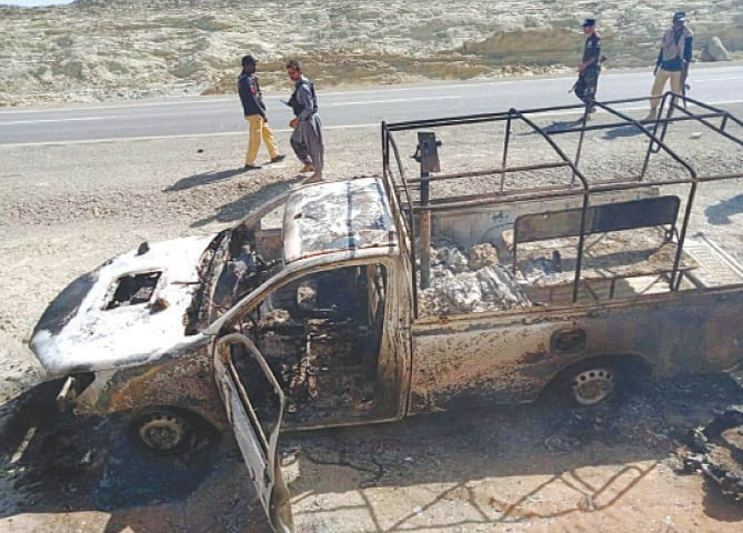SECURITY personnel examine the area around the damaged vehicle after the attack in Ormara on Thursday.—PPI