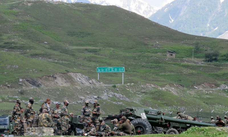 Indian army soldiers rest next to artillery guns at a makeshift transit camp before heading to Ladakh, near Baltal, southeast of Srinagar. — Reuters/File