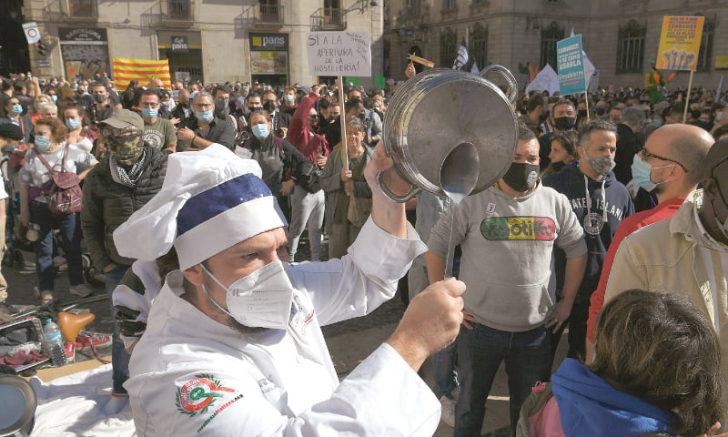 BARCELONA: A cook bangs a pot during a demonstration on Friday to protest restrictions on bars and restaurants imposed by the government of Spain's Catalonia region to fight Covid-19 disease.—AFP