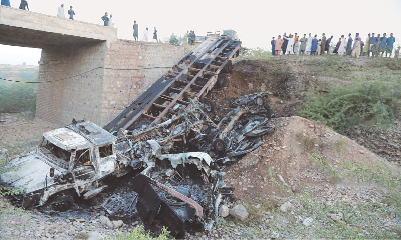 A VIEW of a Nato trailer and other vehicles burnt by armed men on Friday.—Dawn
