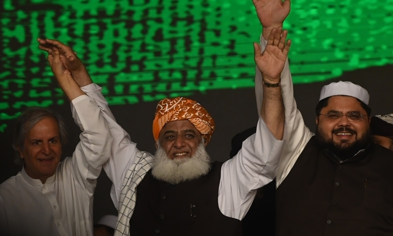 Leader of the newly-formed Pakistan Democratic Movement Maulana Fazlur Rehman (C), Javed Hashmi (L) and Awais Noorani(R) raise their hands in solidarity during the first public rally in Gujranwala on October 16. — AFP