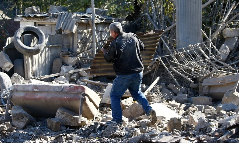A man removes the debris of a building following recent shelling during a military conflict over the breakaway region of Nagorno-Karabakh in Stepanakert on October 17. — Reuters