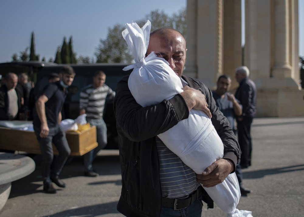 Timur Haligov, an Azerbaijani Turkish father, embraces the body of his 10-month-old baby girl, Narin, who was killed by overnight shelling by Armenian forces during a funeral ceremony, in Ganja, Azerbaijan on Oct 17. — AP