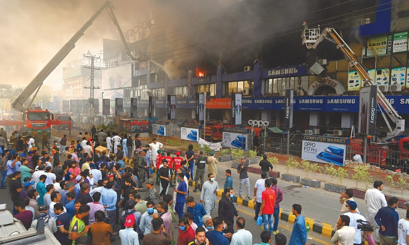 LAHORE: Rescue 1122 firefighters trying to put out a blaze at Hafeez Centre on main Boulevard Gulberg on Sunday.—M. Arif / White Star