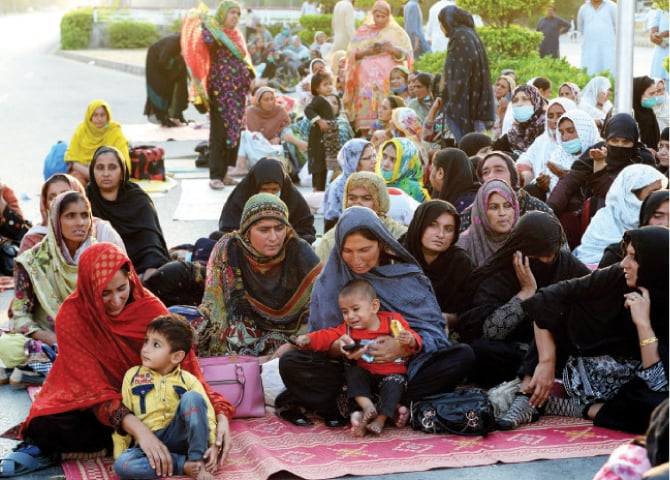 Lady health workers sit with their children on Jinnah Avenue in Islamabad on Sunday. — White Star