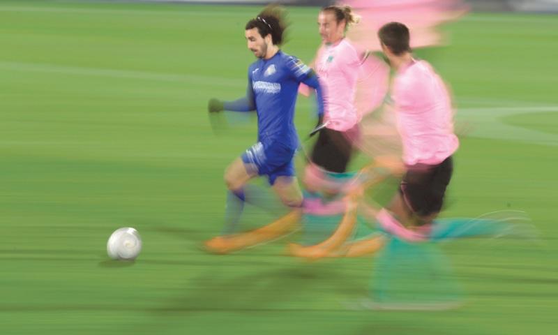 GETAFE: Getafe's Marc Cucurella runs past Barcelona's Antoine Griezmann during their La Liga match at the Coliseum Alfonso Perez —AP