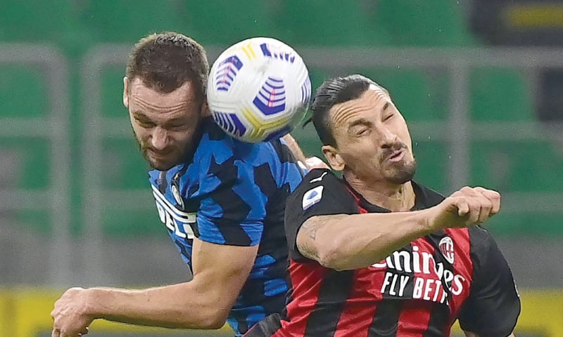 MILAN: Inter Milan's Stefan de Vrij (L) fights for the ball with AC Milan's Zlatan Ibrahimovic during their Serie A match at the San Siro.—AFP