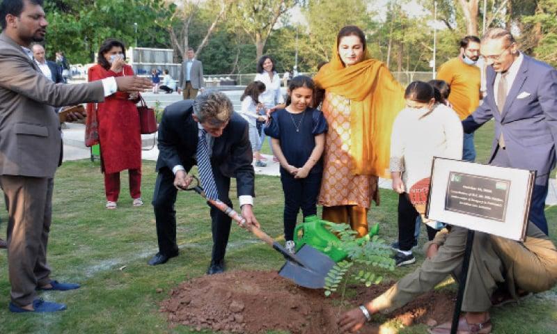 Hungarian Ambassador Béla Fazekas plants sapling in the Gulistan-i-Fatima Park in E-7 on Monday. Pak-Hungary Parliamentary Friendship Group Chairperson MNA Mehnaz Akbar Aziz is also present. — Dawn