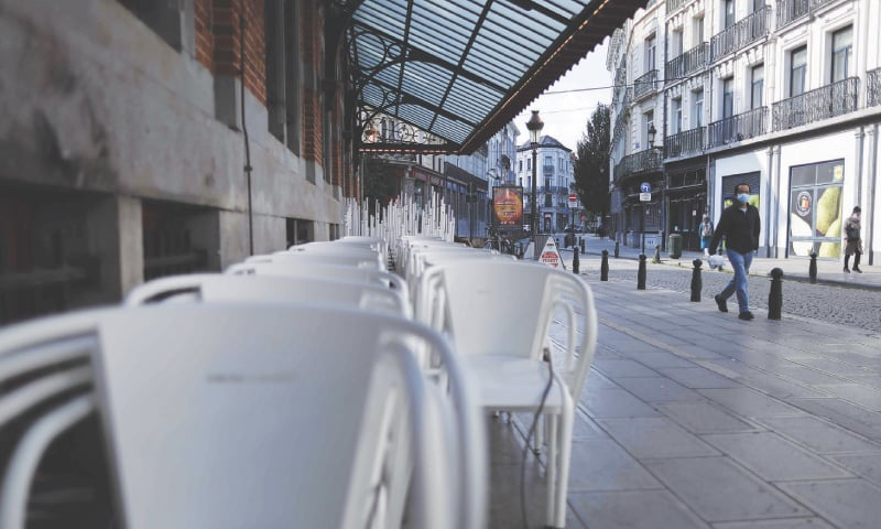 CHAIRS are stacked outside a closed restaurant in Brussels on the implementation day of new sanitary measures aimed at curbing the spread  of the Covid-19. — AFP