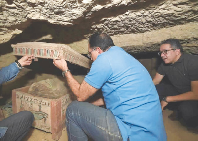 CAIRO: Archeologists open a sarcophagus unearthed in a vast necropolis south of Cairo.—AP