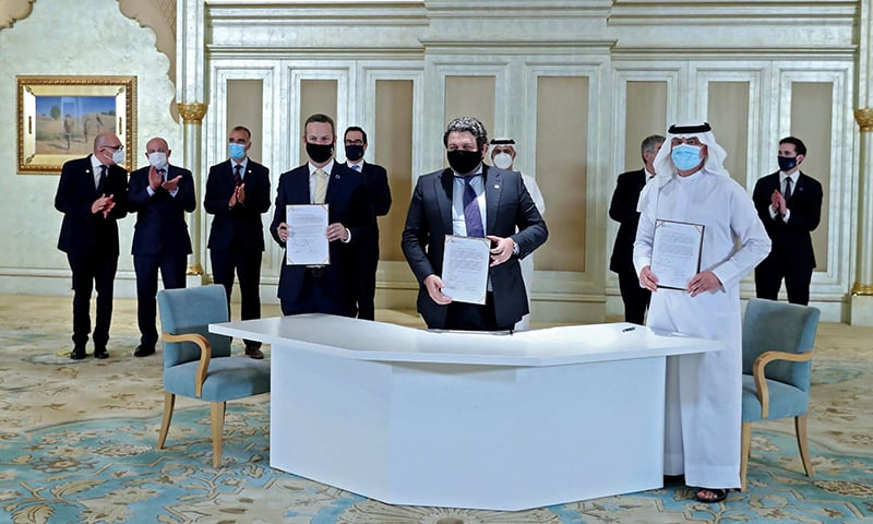 A handout image provided by United Arab Emirates News Agency (WAM) shows Emirati and Israeli delegates signing an agreement at the first Abraham Accords Business Summit in Abu Dhabi on October 19, in the presence of US Treasury Secretary Steven Mnuchin (back-C). — AFP