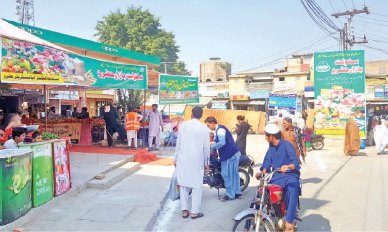 People purchase commodities from the Sahulat Bazaar in Hazro on Tuesday — Dawn