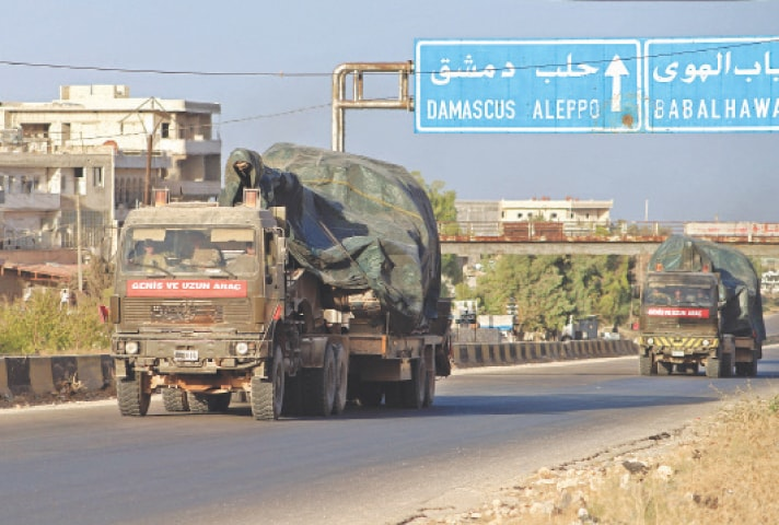 ARIHA (Syria): Turkish military vehicles drive through this town in Idlib province on Tuesday after vacating a post in the countryside.—AFP