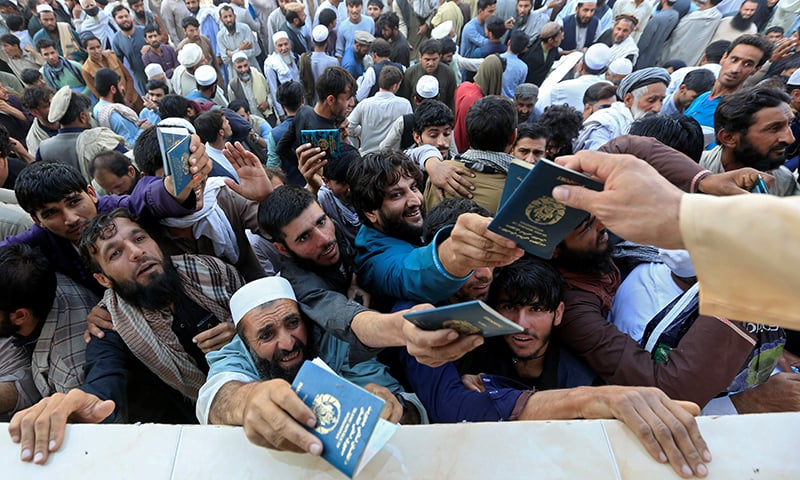 Afghan men wait to collect tokens needed to apply for the Pakistan visa, in Jalalabad, Afghanistan on October 21. — Reuters
