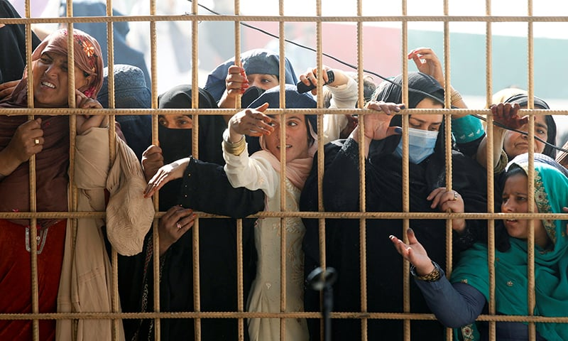 Afghan women wait to receive tokens needed to apply for the Pakistan visa after some people were killed in a stampede in Jalalabad on October 21. — Reuters
