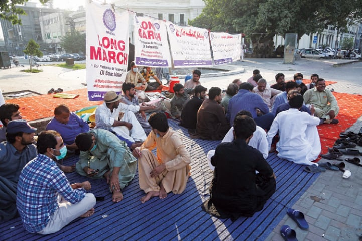 Baloch students sit in front of the Punjab Assembly building. — White Star