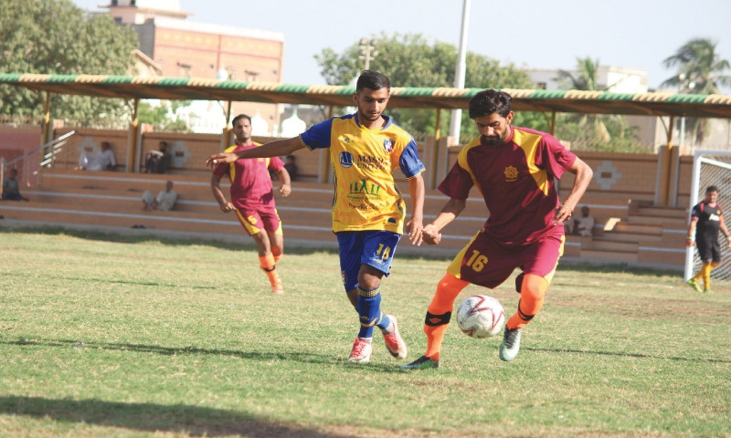 KARACHI: Players of Masha United and Railways in action during their Pakistan Football Federation League match at the Drigh Road Union Ground on Friday.—PFF