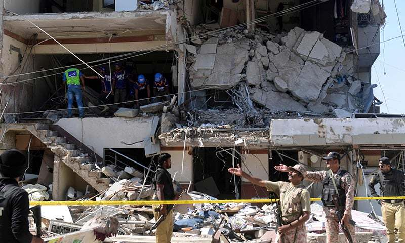 Security personnel and rescue workers are seen amid the debris of a multi-storey building that was damaged after an explosion in Karachi on October 21. — AFP