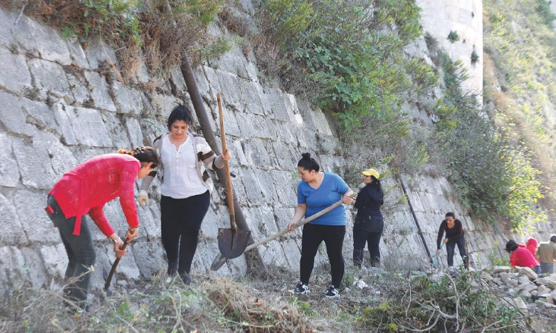 Volunteers take part in a clean-up at the medieval Crusader fortress Krak des Chevaliers, approximately 40 kilometres west of Syria's central city of Homs and close  to the border with Lebanon.—AFP