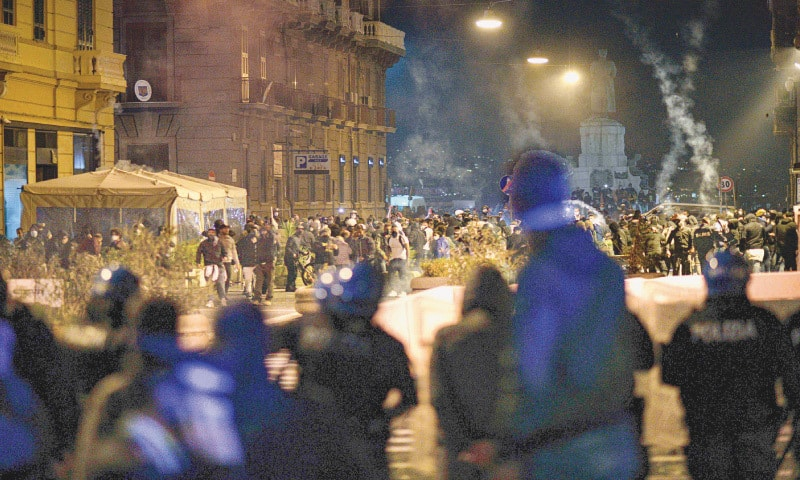 Naples (Italy): Police look at protesters throwing flares in Naples on Friday night. The protesters clashed with  police over a 11pm-to-5am curfew by the government to put the region under lockdown to try to tame surging  Covid-19 infections. — AP