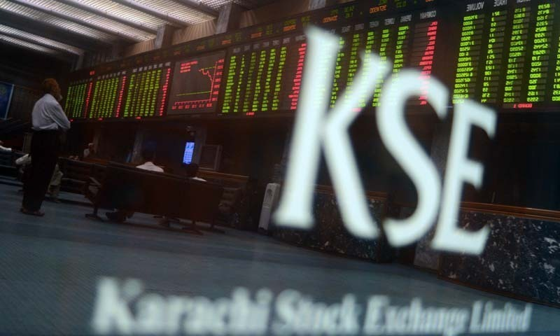 Pakistani stockbrokers watch the latest shear prices on a digital board during a trading session at the Karachi Stock Exchange (KSE) in Karachi. — AFP/File