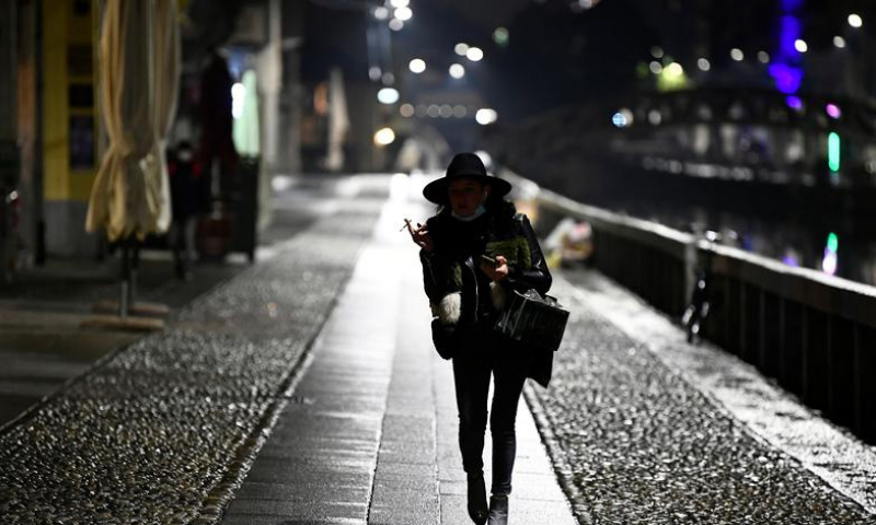 A woman walks on Navigli Grandi as the region of Lombardy imposes a curfew after being hit by a surge of coronavirus infections, in Milan, Italy. — Reuters