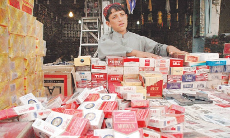A child sells cigarettes to support his family in a push-cart at a market  in Quetta. — File photo