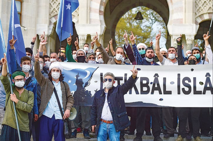 ISTANBUL: Protesters raise their fingers during a demonstration against the French president on Sunday.—AFP