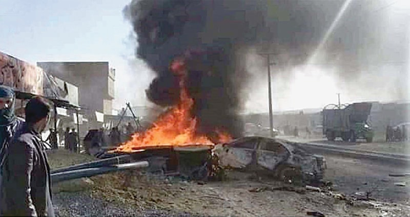 QUETTA: People look at a fire caused by the bomb blast in the Hazarganji area on Sunday.— INP