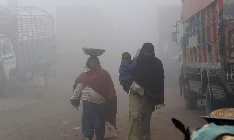 A Pakistani family walk during dense fog and smog in Lahore on December 24, 2018. — AFP/File