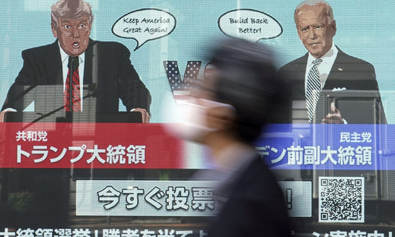 A man wearing a protective mask to help curb the spread of the coronavirus walks past a screen showing illustrations depicting US President Donald Trump, left, and Democratic candidate and former Vice President Joe Biden. — AP
