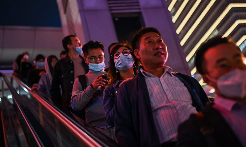 In this picture taken on October 25, people wearing face masks as a preventive measure against the coronavirus commute on an escalator in the financial district of Lujiazui in Shanghai. — AFP