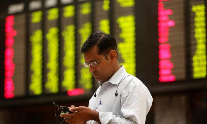 A man uses his cell phone as he stands in front of a display board showing stock prices during a trading session in the halls of Pakistan Stock Exchange in Karachi. — Reuters/File