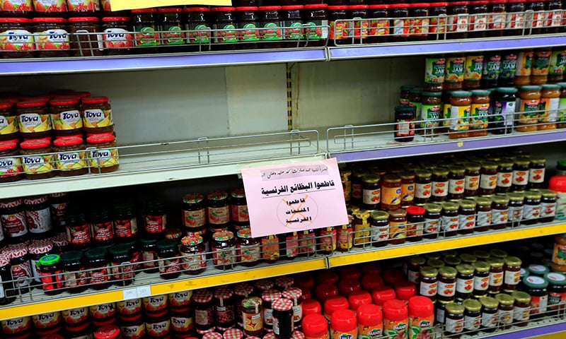 Signs in Arabic calling customers to boycott French products are placed on shelves at a supermarket in the Yemeni capital Sanaa. — AFP