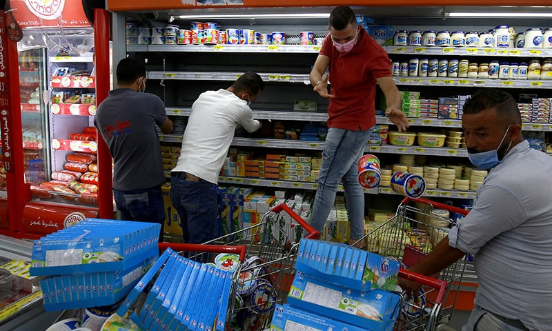 Workers at a supermarket in the Jordanian capital Amman remove French products off shelves during a boycott of French products on October 26. — AFP