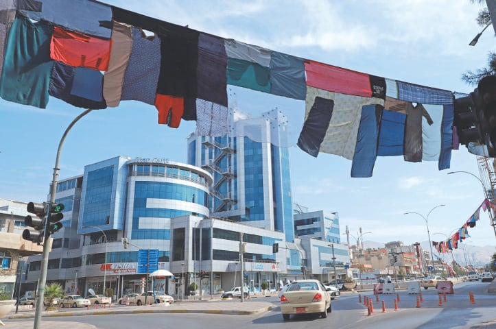 SULAIMANIYAH: Cars pass beneath an artwork by visual artist Tara Abdallah, hanging above a highway in this city in Iraq's autonomous Kurdish region.—AFP