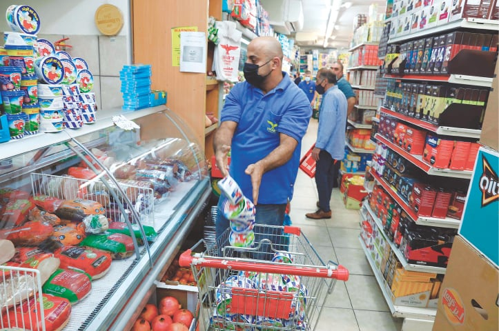 A worker removes French goods from the shelves of a supermarket in the Arab neighbourhood of Beit Hanina in Israeli-annexed east Jerusalem on Monday. — AFP