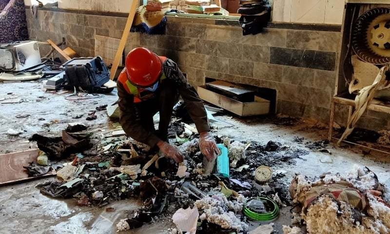 A rescue worker examines remains at the site of a blast at a madressah in Peshawar on October 27. — AFP