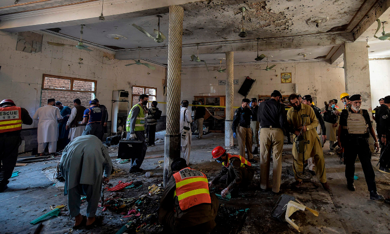Security officials examine the site of a blast at a madressah in Peshawar on Tuesday. — AFP