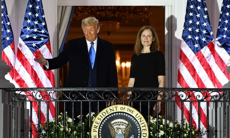 US President Donald Trump gestures next to Judge Amy Coney Barrett on the Truman Balcony after she was sworn in as a US Supreme Court Associate Justice on October 26. — AFP