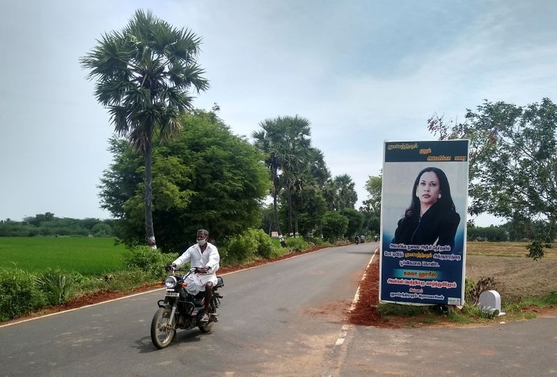 A man drives past a banner of US Democratic vice presidential nominee Kamala Harris at the entrance to the village of Thulasendrapuram, where Harris' maternal grandfather was born and grew up, in the southern Indian state of Tamil Nadu, India, on October 25. — Reuters