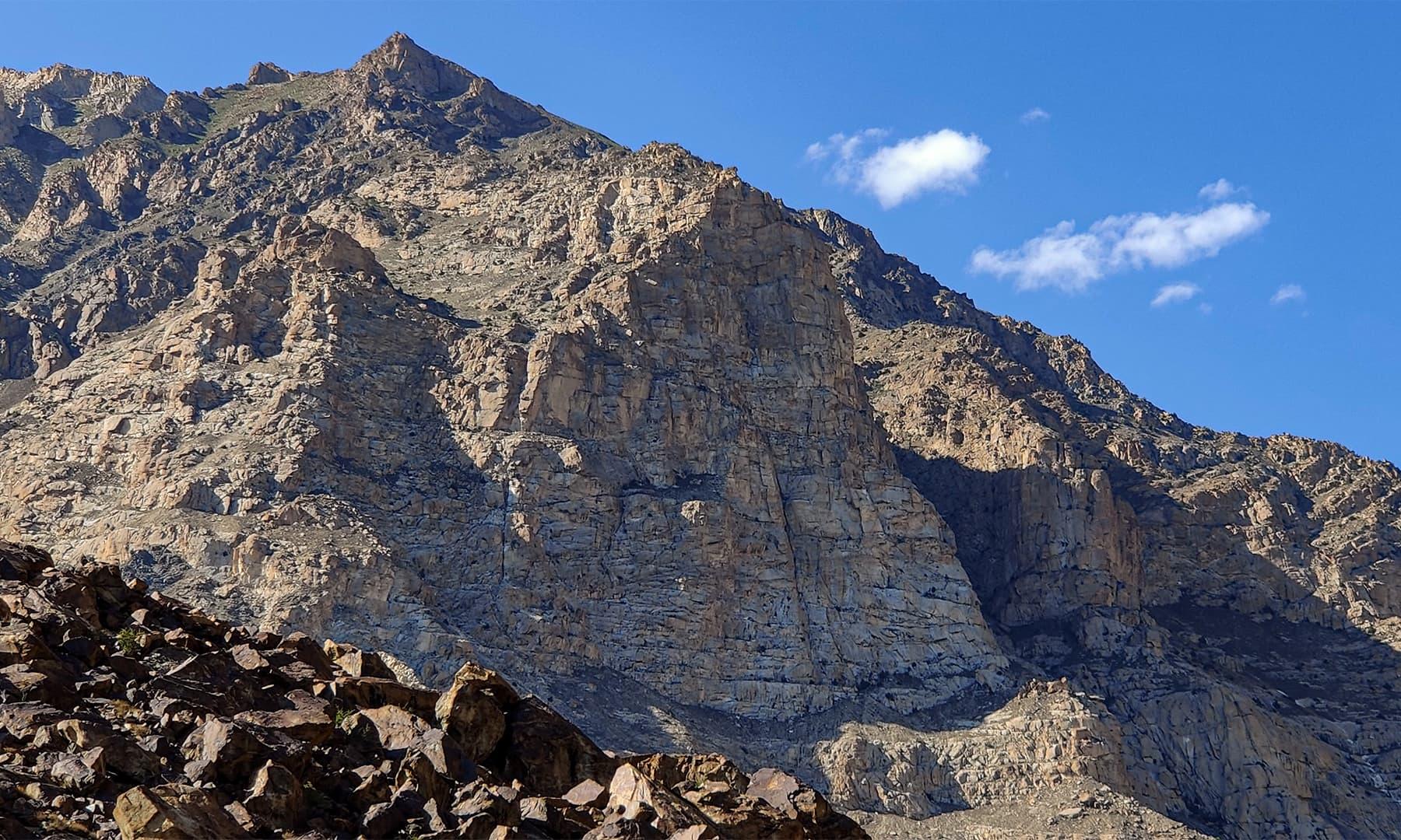 سرمئی رنگ کے یہ پہاڑ جھیل کے قریب ہونے کا پتا دیتے ہیں