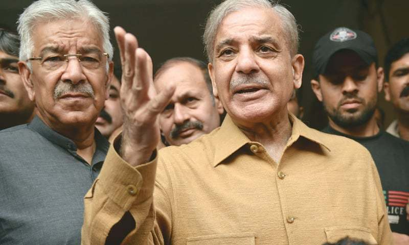 In this 2019 file photo,  PML-N president Shahbaz Sharif, accompanied by party leader Khawaja Asif, speaks about the health of his brother and former premier Nawaz Sharif. — AP