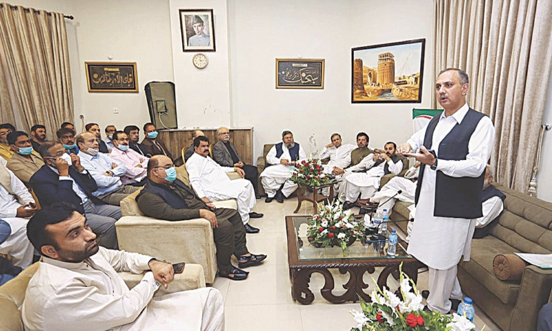 FEDERAL Energy Minister Omar Ayub Khan speaks to the business community in Hyderabad circuit house on Wednesday. — APP