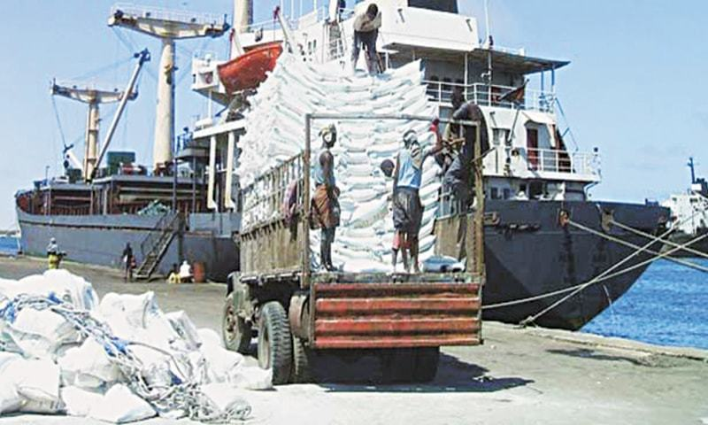 Porters load bags of sugar on an unidentified cargo ship at the Karachi seaport. — Reuters file photo