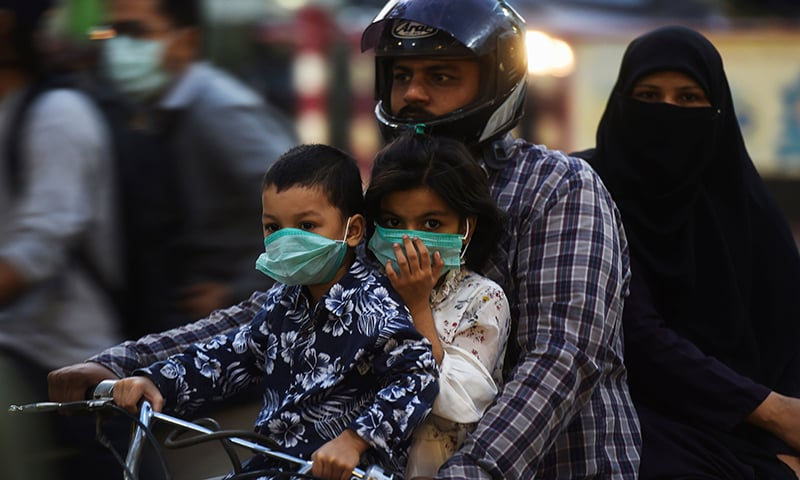 Children riding on a bike with their family wear facemasks as a preventive measure against the coronavirus in Karachi on October 29. — AFP