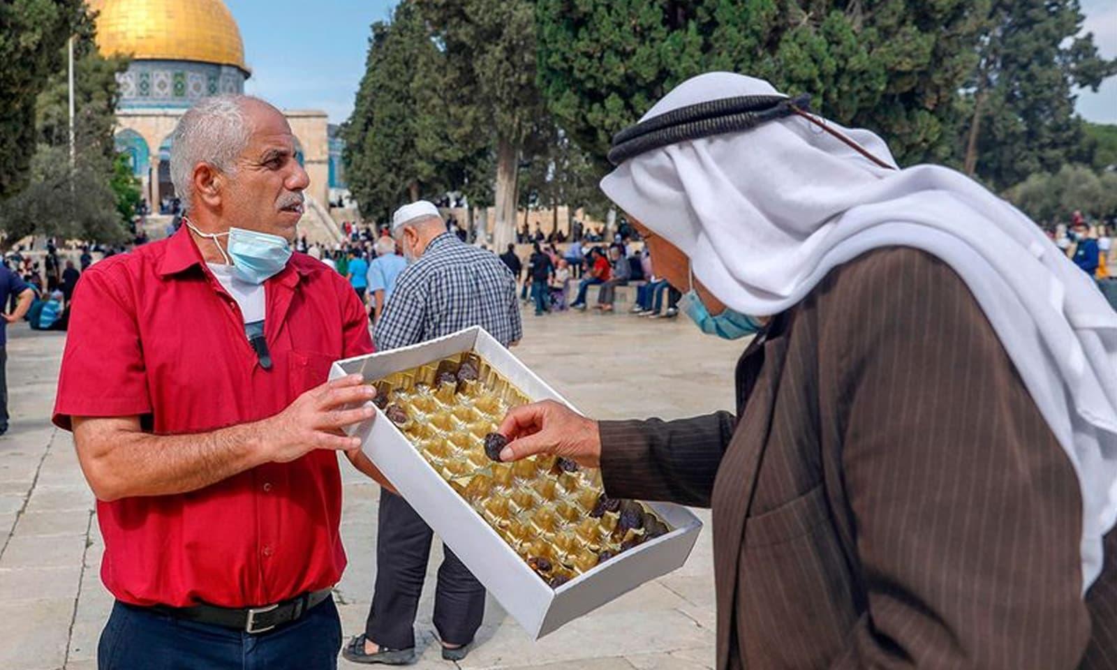 فلسطین میں ایک شخص لوگوں میں مٹھائی تقسیم کر رہا ہے— فوٹو:اے ایف پی