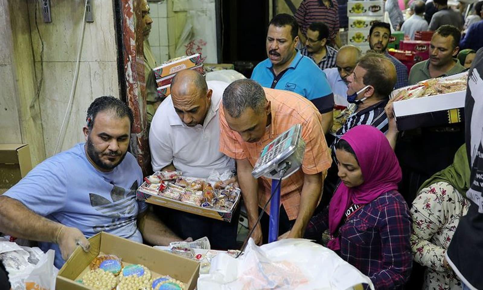 مصر میں لوگ مٹھائی خرید رہے ہیں— فوٹو:رائٹرز