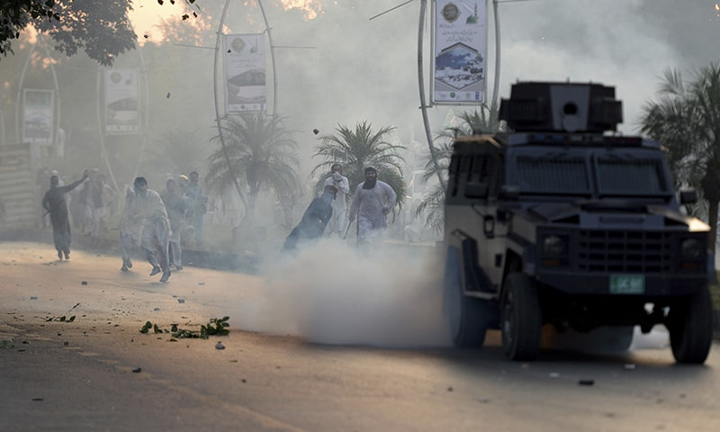 Protesters hurl stones at a police armored vehicle after police fired tear gas shells to disperse them and prevent them from marching toward the French Embassy at a rally in Islamabad, Friday. — AP