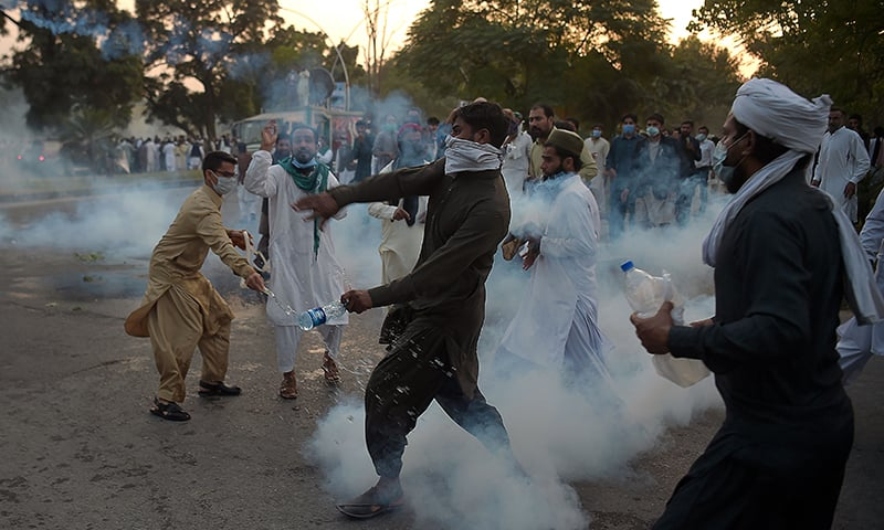 Protesters return tear gas shells during a demonstration in Islamabad on October 30. — AFP